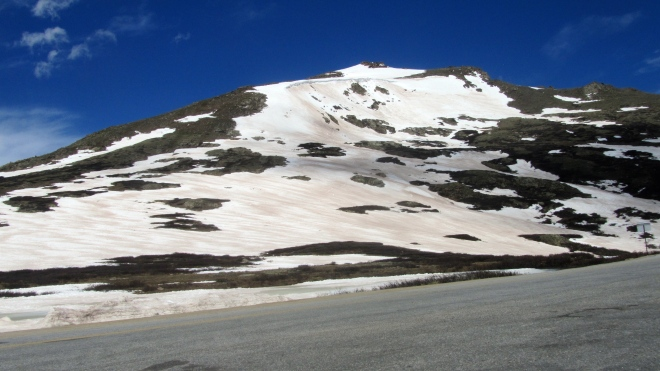 Windswept mountain top with summer snow