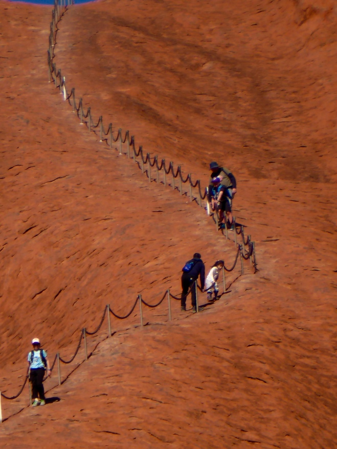 Some tourists climb Uluru