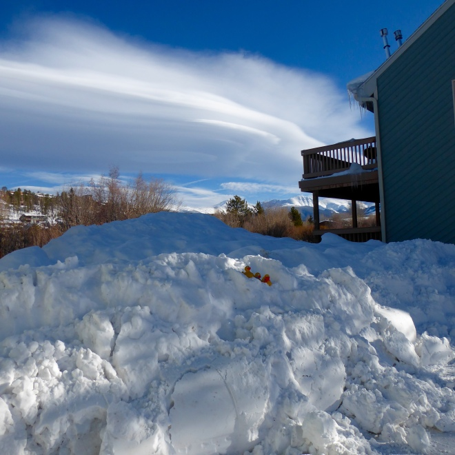 Snow pile and swirling clouds