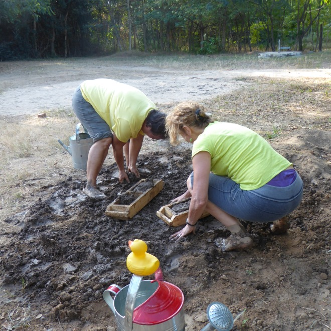 Barefoot in the mud. Filling brick molds with mud for bricks