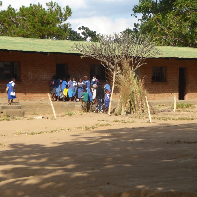 Children in uniforms entering school
