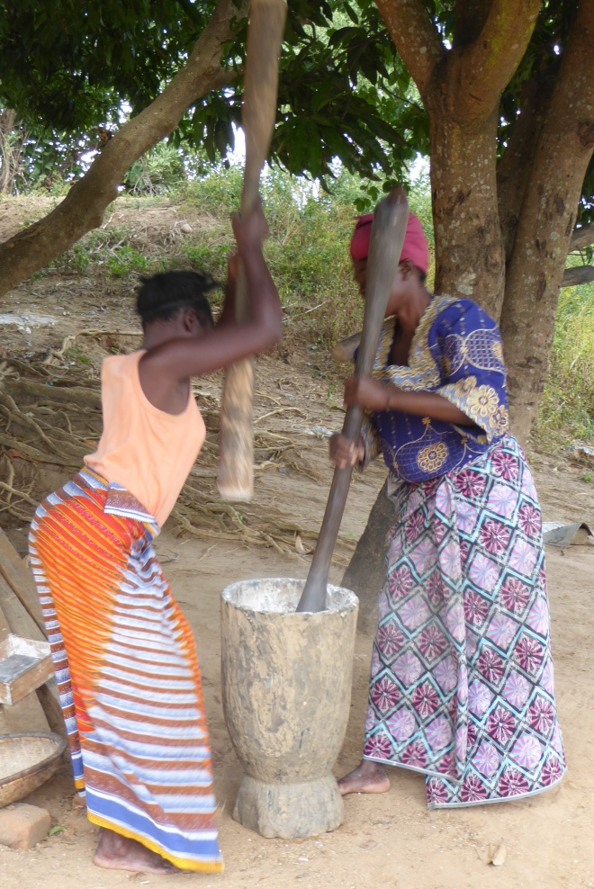 Rebecca and Catherine pound cassava together