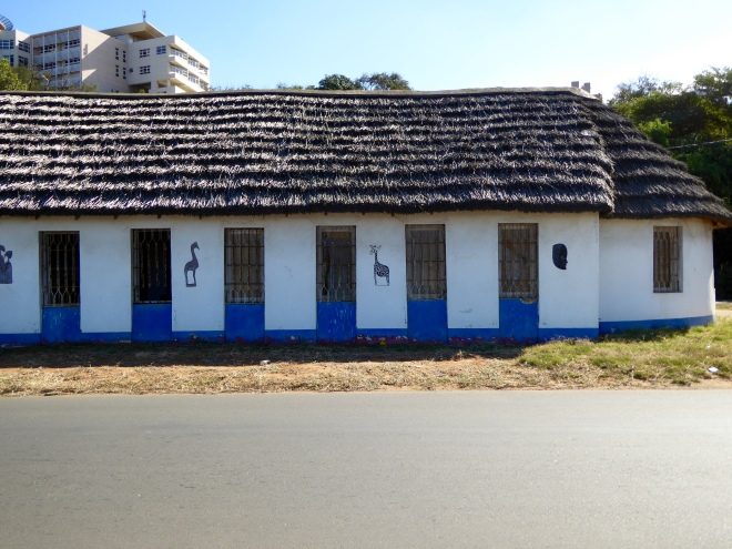 Old building with thatched roof. Zeb on ground under giraffe