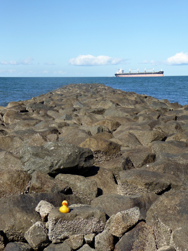 Rocks at end of pier and ship on Maputo Bay